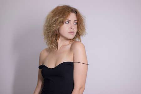 emotional portrait of a beautiful curly blonde-redhead in black undershirt. High quality photo Imagens