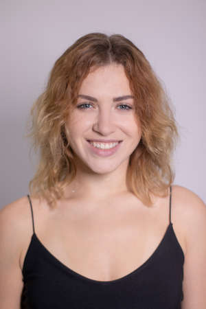 emotional portrait of a beautiful curly blonde-redhead in black undershirt. High quality photo