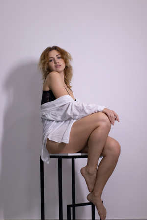 emotional portrait of a beautiful curly blonde-redhead in black undershirt and white shirt sitting on a high bar-chair. High quality photo Imagens