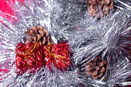 new years decorations - red presents, cones and snowflakes in silver tinsel for christmas tree.