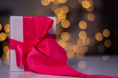 white gift box with pink ribbon bow on gold bokeh background.