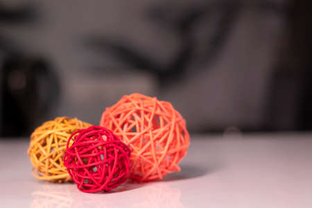 orange, red and pink wicker balls for decoration on a white table.