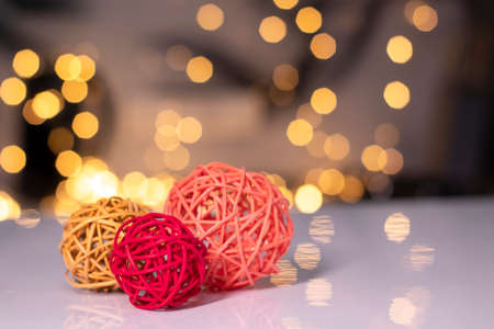 orange, red and pink wicker balls for decoration on a background of golden bokeh.