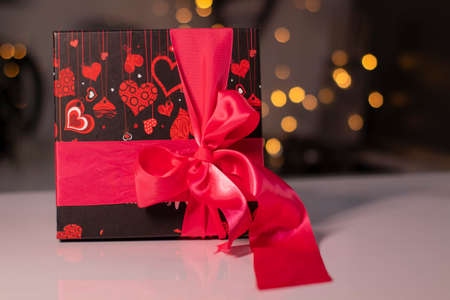 black with hearts gift box with pink ribbon bow on gold bokeh background.