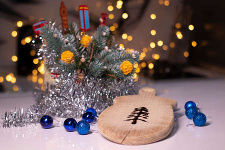 christmas tree made of chocolate on a wooden board next to new years decorations.