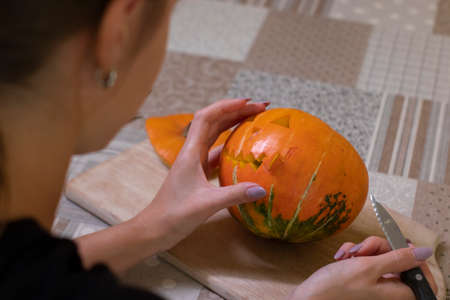 the process of making a Halloween pumpkin. cutting out the mouth by brunette girl. Stok Fotoğraf