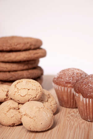 muffins, almond amaretti and oat cookies on wooden stand board. concept of sweet bakery