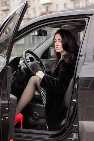 portrait of a fabulous brunette wearing checkered dress and red high-heeled shoes in a lux car. woman in automobile