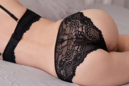 close up of slim woman body in black lace lingerie on grey background. Erotic ladies concept. Banque d'images