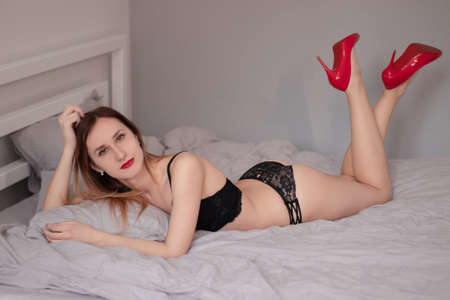 Sexy seductive woman in black lingerie and luxurious red high heeled shoes on bed with grey sheets.