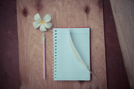 piuma bianca: blank notebook with White Feather  and pen on wooden table