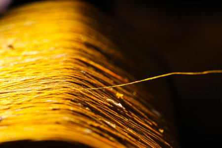 fill up: gold raw silk thread , black background,selected focus Stock Photo