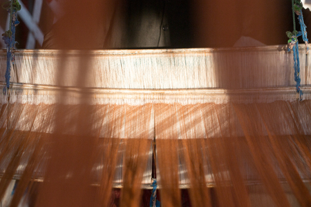 silk thread: orange silk thread in sewing or weaving machine,texture,background