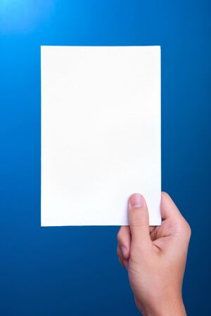 hand holding white sheet paper card on blue background