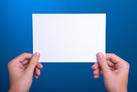 hands holding white sheet paper card on blue background Stock Photo