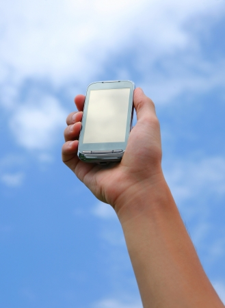 Hand holding smart phone in the sky