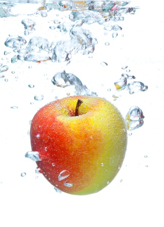 fresh apple falling into water with splash and bubbles on white Stock Photo