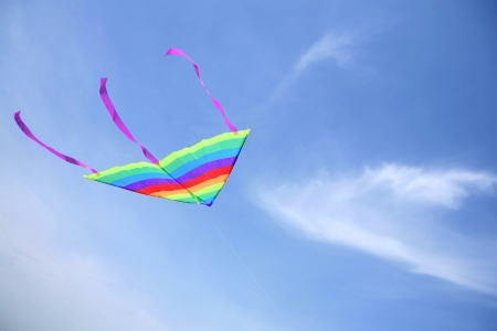 colorful kite flying up in blue sky Stock Photo