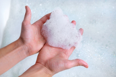 hands holding soap foam above bathtub