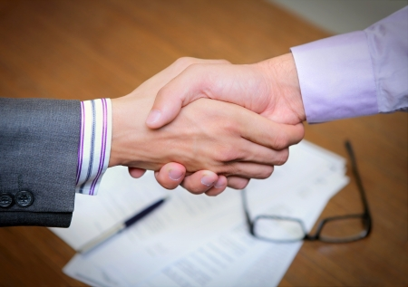hands shaking business over a business contract