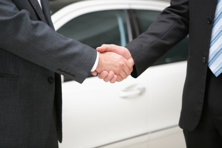 two businessmen shaking hands over luxury car deal Stock Photo