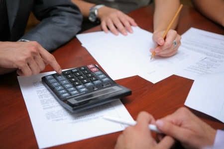 Business people calculating budget together in office