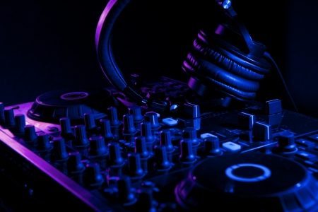 dj mixer with headphones in nightclub