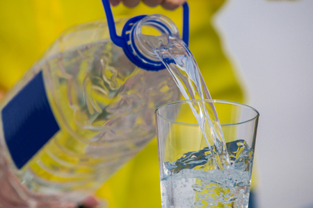 Beautiful healthy woman pours into a glass of drinking water in yellow clothes, isolated on white background