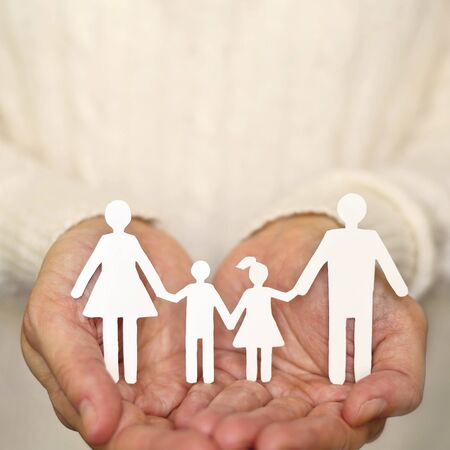 hand care: Womans hands holding paper family Stock Photo