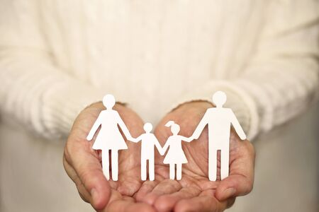 Womans hands holding paper family Stock Photo