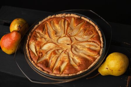 Tasty homemade pear pie on wooden background