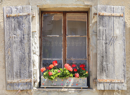 Beautiful old window with red flowers