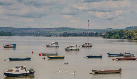 dinghies: Many small fishing boats anchored on Danube river with beautiful blue sky. View from Zemun part of Belgrade, Serbia.
