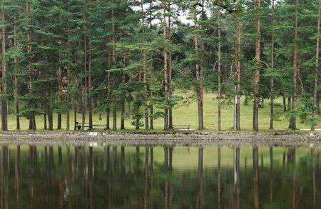 to the other side: Pond on Zlatibor Mountain in Serbia and promenade on the other side with people resting on benches Stock Photo