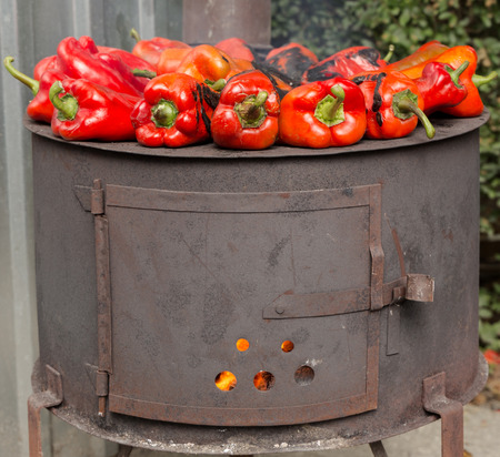 roasting: Roasting red paprika on range for winter provisions , autumn season