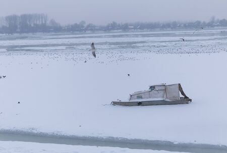 lido: Frozen river Danube at -15C, with small fishing boat and birds Stock Photo