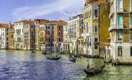 streetlife: View on grand canal and gondoliers, and fantastic multi color buildind in Venice Italy
