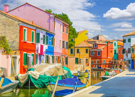 Part of canal, many boats, beautiful sky scape and colorful houses on Burano Island, Adriatic sea, Venice Italy