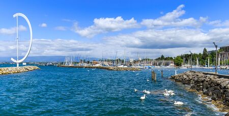 View on yachts and boats at Ouchy port with the blue spring sky on the background and beautiful swans. Lausanne, Switzerland