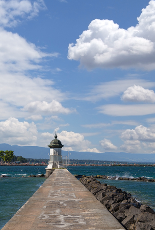 mol: Lighthouse on lake Leman, stone embankment and beautiful summer sky. Geneva Switzerland