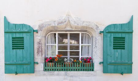 louver: Window with the multicolor flowers in old house. Small village Gruyere, canton Fribourg Switzerland.