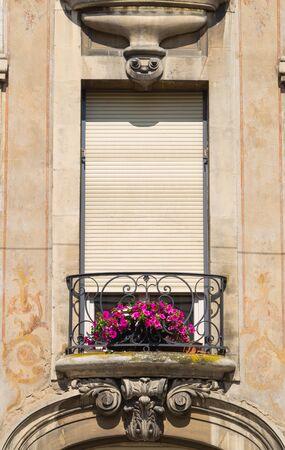 Hermosa ventana y flores violetas en el balcón. Ciudad de Dijon, provincia de Bourgogne Franche-Comte. Francia Foto de archivo - 83093529