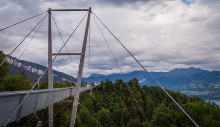 pedestrian bridge: View on big iron pedestrian bridge over the deep forest with cloudy sky and beautiful Swiss alps. City of Sigriswil, canton Bern, Switzerland