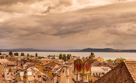 Beautiful view on lake Neuchatel with beautiful sky scape, part of city of Neuchatel and old watch on the tower. Canton Neuchatel, Switzerland, sephia