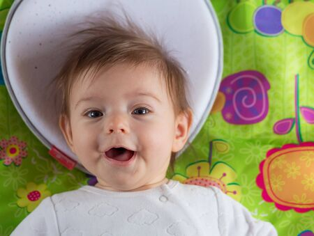 Wonderful smiling baby girl on the multicolor flor