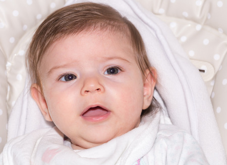 Cute little baby girl wrapped in white pyamas in close-up Stock Photo