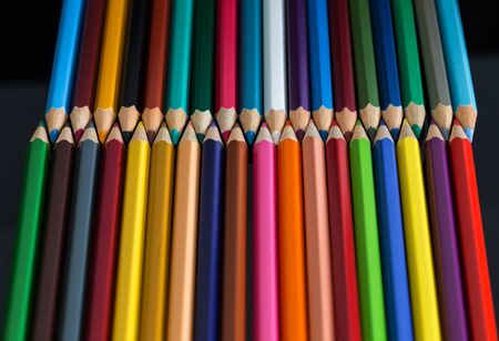 Pile of multicolored wooden crayon isolated on the black background with the reflection.
