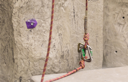 Carabiner, spit and climbing rope. Free climbing gear. Artificial climbing bouldering wall indoors Archivio Fotografico