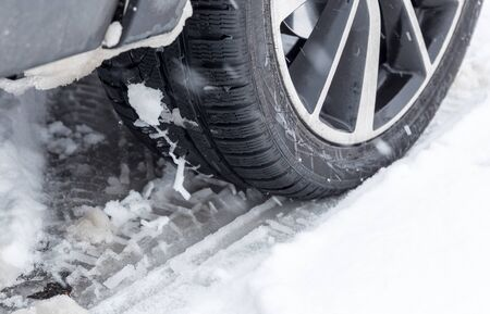 Closeup of car tires in winter at the snowing day