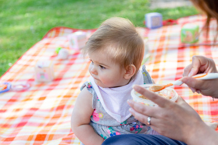 Mother feeding baby with spoon full of porridge in the garden. Outdoor photography